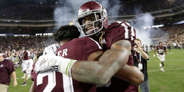 Texas A&M wide receiver Kendrick Rogers, right, celebrates with Charles Oliver (21) after an NCAA college football game against LSU Saturday, Nov. 24, 2018, in College Station, Texas. Texas A&M won 74-72 in seven overtimes.(Associated Press)