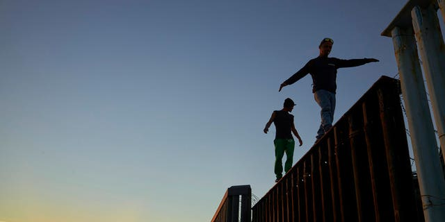 Two Central American migrants walk along the top of the border structure separating Mexico and the United States Wednesday, Nov. 14, 2018, in Tijuana, Mexico. Migrants in a caravan of Central Americans scrambled to reach the U.S. border, catching rides on buses and trucks for hundreds of miles in the last leg of their journey Wednesday as the first sizable groups began arriving in the border city of Tijuana. (AP Photo/Gregory Bull)