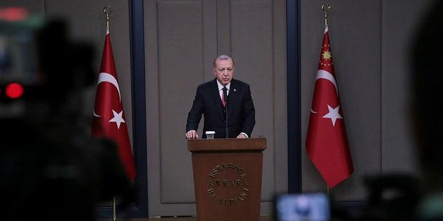 Turkey's President Recep Tayyip Erdogan talks to members of the media at the airport in Ankara, Turkey, Saturday. (Presidential Press Service via AP)