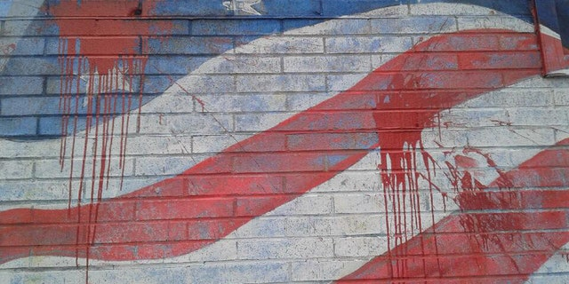 The American flag mural on the side of La Bella Pizza Bistro was vandalized Monday night. Police are investigating the situation.