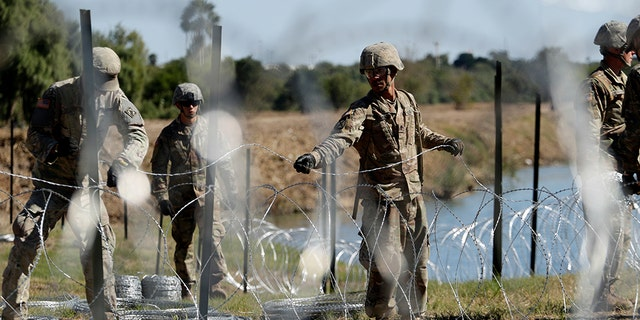 FILE - In this Nov. 16, 2018, photo, members of the U.S. military install multiple tiers of concertina wire along the banks of the Rio Grande near the Juarez-Lincoln Bridge at the U.S.-Mexico border in Laredo, Texas. The Pentagon is estimating the cost of the military's mission on the U.S.-Mexico border will be about $210 million under current plans. (AP Photo/Eric Gay)