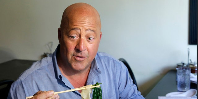 """In this Thursday, July 20, 2017, file photo, Travel Channel's """"Bizzare Foods"""" host Andrew Zimmern, a four-time James Beard award-winning chef, samples Taiwanese noodle soup and pork roll at Happy Stony Noodle in Elmhurst, Queens in New York."""