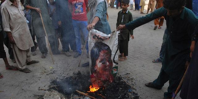 Pakistani protesters burn a poster image of Christian woman Asia Bibi in Hyderabad, Pakistan.