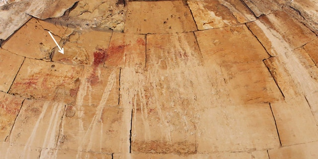 Remnants of the baptism-of-Christ scene (indicated by white arrow) on the apse of the Baptistry chamber. (Photograph by Dror Maayan/Antiquity)