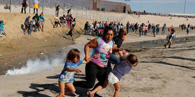 A migrant family, part of a caravan of thousands traveling from Central America en route to the United States, running away from tear gas in front of the border wall between the U.S and Mexico in Tijuana on Sunday.