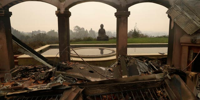 A Buddha statue stands among the damage caused by a wildfire at a home in Malibu, Calif.