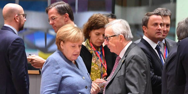 German Chancellor Angela Merkel, left, speaks with European Commission President Jean-Claude Juncker during a round table meeting at an EU summit in Brussels, Sunday, Nov. 25, 2018.