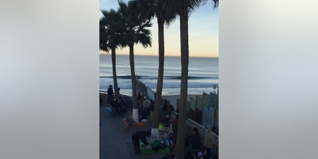 About two dozen migrants who arrived in Tijuana are camped out next to the border fence near the ocean. Others have crammed into already overcrowded shelters or are sleeping in tents.
