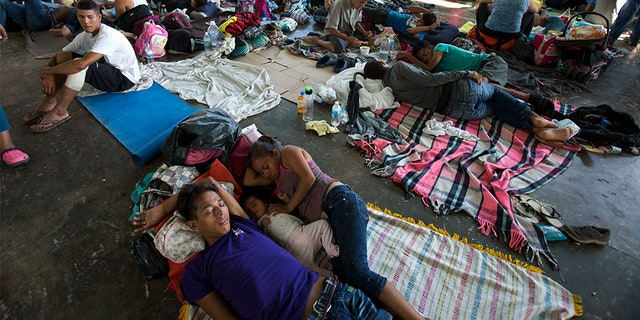 People rest on the ground in a municipal lot serving as a makeshift campground, as a caravan of Central Americans hoping to reach the U.S. border takes a rest day in Juchitan, Mexico, on Wednesday.
