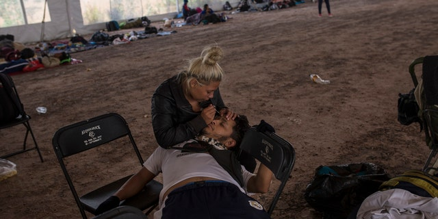 Central American migrant Jenifer Argueta plucks the eyebrows of Honduran Kevin Banegas, while waiting to receive donated food in Palmillas, Mexico, Saturday, Nov. 10, 2018.