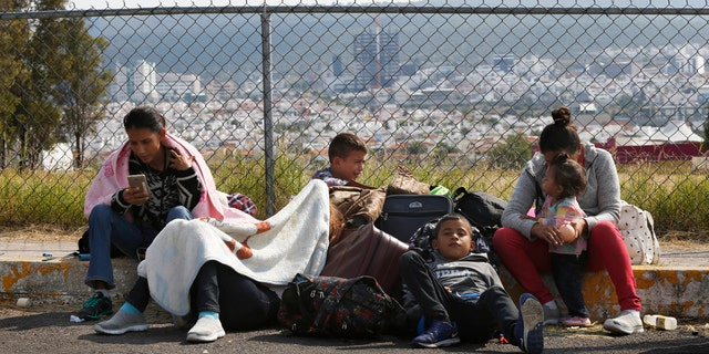 Central American migrants rest outside a soccer stadium after arriving in Queretaro, Mexico, as they resume their journey north.