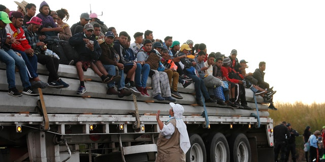 A Catholic nun gives travel advice to Central American migrants riding in the bed of a semi-trailer, as they move toward the U.S. border.