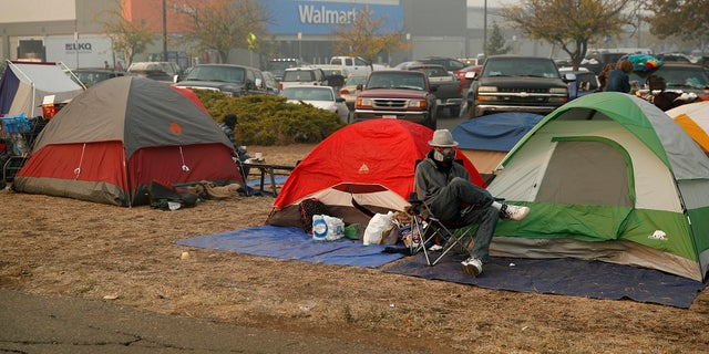 People sit by their tents at a makeshift encampment outside a Walmart store for people displaced by the Camp Fire.