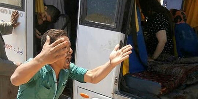 A man screams beside a bus carrying Coptic Christians which came under attack outside Cairo, Friday, Nov. 2, 2018.