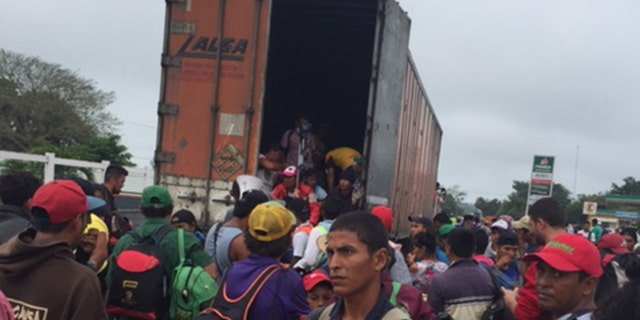 Migrants rush to get into truck as they continue trek to U.S. border on Sunday, November 4, 2018.