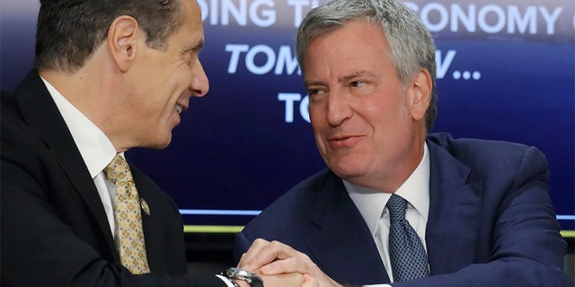 New York Gov. Andrew Cuomo, left, and New York City Mayor Bill de Blasio shake hands during a news conference Tuesday announcing the Amazon deal. Members of their own party are now criticizing the incentives package being offered to Amazon.