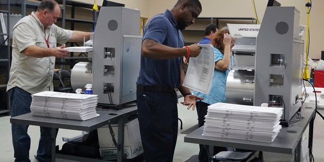 Election workers place ballots into electronic counting machines at the Broward Supervisor of Elections office in Lauderhill. The Florida recount began Sunday morning in Broward County. (Joe Cavaretta /South Florida Sun-Sentinel via AP)
