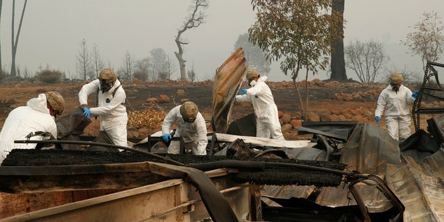 Members of the California Army National Guard search a property for human remains at a home burned in the Camp fire, Wednesday, Nov. 14, 2018, in Paradise, Calif.