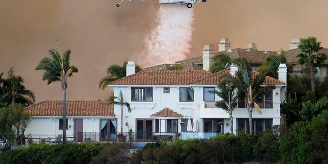 A helicopter drops water on a brush fire behind a home during the Woolsey Fire in Malibu, Calif., Friday, Nov. 9, 2018.