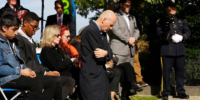Hugh Hales-Tooke, a friend of victim Nicholas Cleves, kneels during a moment of silence during a ceremony marking the anniversary of the Hudson River Park bike path attack.