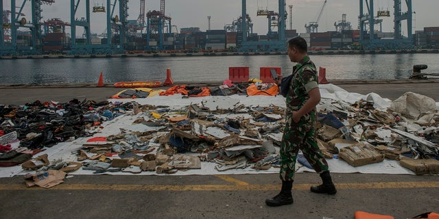 An Indonesian soldiers walk past debris retrieved from the waters where Lion Air flight JT 610 is believed to have crashed at Tanjung Priok Port in Jakarta, Indonesia, Wednesday, Oct. 31, 2018.