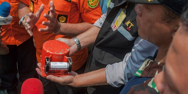 A member of National Transportation Safety Committee holds the flight data recorder from the crashed Lion Air jet on board of a research ship Baruna Jaya anchored in the waters of Tanjung Karawang, Indonesia on Thursday.