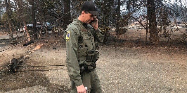 California Department of Fish and Wildlife warden Jake Olsen tells his wife her wedding ring was found in the ashes of their home they share with their four children in Paradise, Calif.