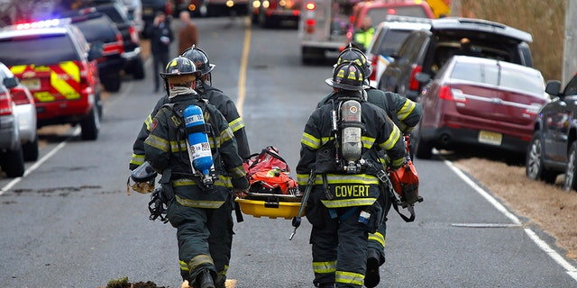 Firefighters carry a stretcher to the scene of a fatal fire at 15 Willow Brook Rd. Tuesday, Nov. 20, 2018, in Colts Neck,N.J.