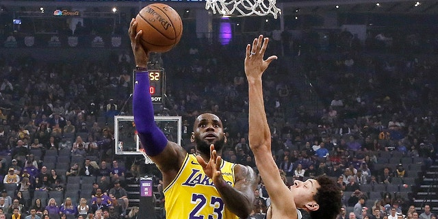Los Angeles Lakers forward LeBron James, center, drives to the basket between Sacramento Kings' Harry Giles III, left, and Justin Jackson during the second half of an NBA basketball game Saturday, Nov. 10, 2018, in Sacramento, Calif.