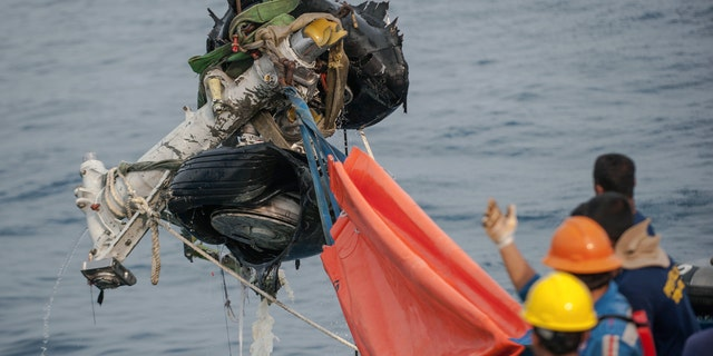 Rescuers use acrane to retrieve part of the landing gears of the crashed Lion Air jet from the sea floor in the waters of Tanjung Karawang, Indonesia, Sunday, Nov. 4, 2018.