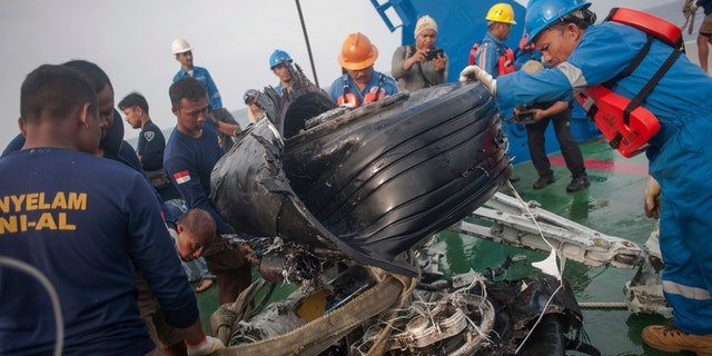 Rescuers inspect part of the landing gears of the crashed Lion Air jet they retrieved from the sea floor in the waters of Tanjung Karawang, Indonesia, Sunday, Nov. 4, 2018.