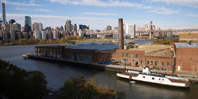 A rusting ferryboat is docked next to an aging industrial warehouse on the Anable Basin, in the Long Island City neighborhood of the Queens borough of New York. Amazon announced Tuesday that this area will house one of its newest headquarters.