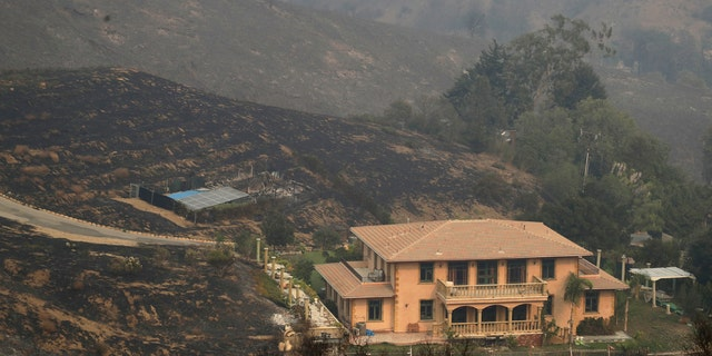 A home is spared after a wildfire swept through Saturday, Nov. 10, 2018, in Malibu, Calif.