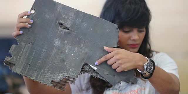 """Grace Nathan, whose mother was on the ill-fated Malaysia Airlines Flight 370, shows a serial number on a piece of debris found in Madagascar that is """"most likely"""" from MH370 at the Ministry of Transport in Putrajaya, Malaysia, Friday, Nov. 30, 2018."""