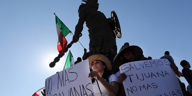 "Demonstrators with signs that read in Spanish: ""No more Caravans"", and ""Let's save Tijuana, no more caravans,"" stand under a statue of indigenous Aztec ruler Cuauhtemoc to protest the presence of thousands of Central American migrants in Tijuana, Mexico, on Sunday."