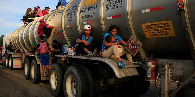 A woman holding her baby hitches a ride on the fender of a tanker in Niltepec, Mexico, on Tuesday.