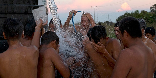 A man filling a water tank on a truck pauses to spray migrants with water to help them shower in Juchitan.
