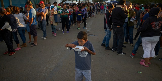 A boy eats as others wait in line for dinner outside of a shelter housing members of the migrant caravan in Tijuana.
