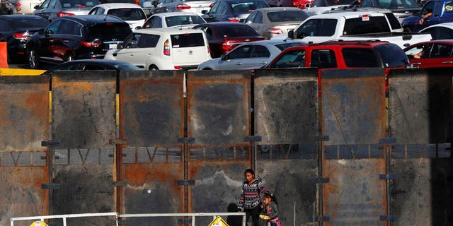 A newly erected barrier wall stands amid cars at the Mexico-U.S. border, as they wait in line to enter the U.S., as they leave Tijuana, Mexico, Monday, Nov. 19, 2018.