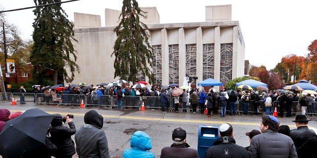People line both sides of the street as they gather outside the Pittsburgh synagogue on Saturday.