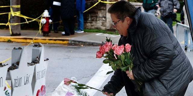 Colleen Cooper lays a single rose on each of the memorials for the eleven people fatally shot last week at the Tree of Life Synagogue after a service, on Saturday in Pittsburgh. (AP Photo/Keith Srakocic)
