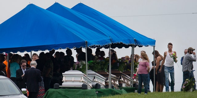 In this May 3, 2016, file photo, mourners gather around caskets for six of the eight members of the Rhoden family found shot April 22, 2016, at four properties near Piketon, Ohio.