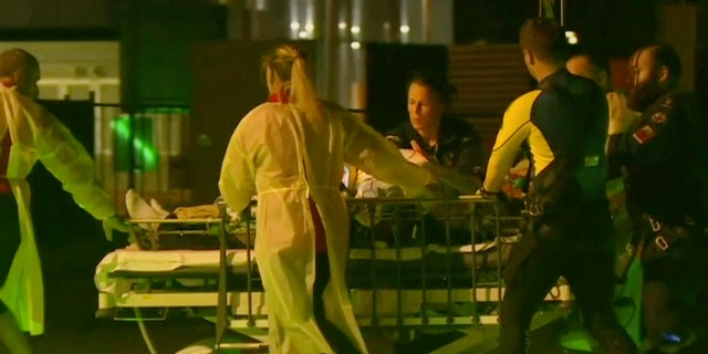 In this Nov. 5, 2018, image made from video, Daniel Christidis, a victim of a shark attack is wheeled on stretcher by paramedics after a rescue helicopter transporting him landed at Mackay Base Hospital helicopter platform in Mackay, Queensland state, Australia.
