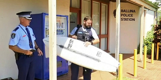 A man has used his surfboard to fend off a shark that bit him on his calf off an Australian beach two days after a fatal attack on the Great Barrier Reef.