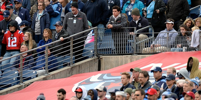 A hole is left in the tarp that covers the Tennessee Titans player entrance to the field as fans watch the Titans play the New England Patriots in the second half of an NFL football game in Nissan Stadium, Sunday, Nov. 11, 2018, (AP Photo/Mark Zaleski)