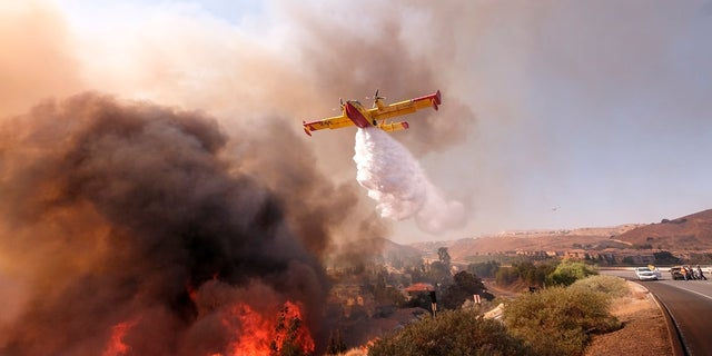 An air tanker seen here dropping water on a fire along the Ronald Reagan Freeway in Simi Valley, Calif., on Monday, Nov. 12, 2018.