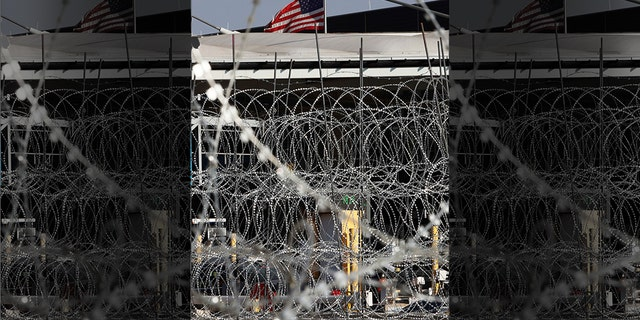 Newly placed barbed wires hangs at the U.S. border fence, where a U.S. flag flies in San Ysidro, seen from Tijuana, Mexico, Monday. The United States closed off northbound traffic for several hours at the busiest border crossing with Mexico to install new security barriers on Monday, a day after hundreds of Tijuana residents protested against the presence of thousands of Central American migrants. (AP Photo/Marco Ugarte)