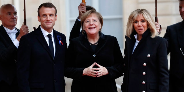 French President Emmanuel Macron and his wife Brigitte, right, welcome German Chancellor Angela Merkel in the courtyard of the Elysee Palace Sunday, Nov. 11, 2018 in Paris.