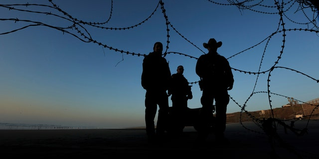 Border patrol officers stand at the beach on the U.S. side of the fence between San Diego and Tijuana, Mexico, Monday, Dec. 24, 2018. Discouraged by the long wait to apply for asylum through official ports of entry, many Central American migrants from recent caravans are choosing to cross the U.S. border wall and hand themselves in to border patrol agents. (AP Photo/Daniel Ochoa de Olza)