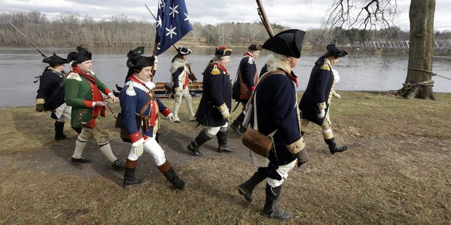 Re-enactor John Godzieba, right, portrays Gen. George Washington as he leads others along the banks of the Delaware River, Tuesday Dec. 25, 2018 in Washington Crossing, Pa.